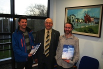 Galway City Council Chief Executive Brendan McGrath being presented with a copy by Kieran Cunnane and Bernard McGlinchey of Transition Galway